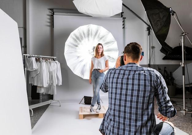 Homem tirando uma foto de um modelo de mulher em estúdio