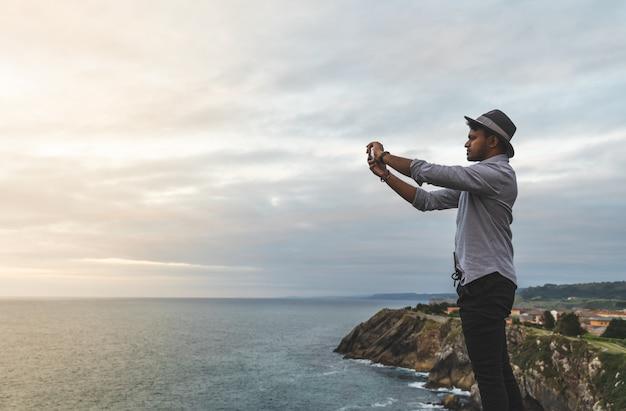 Homem tirando uma foto para o oceano ao pôr do sol