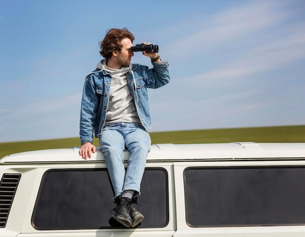 Homem tiro completo com binóculos na van
