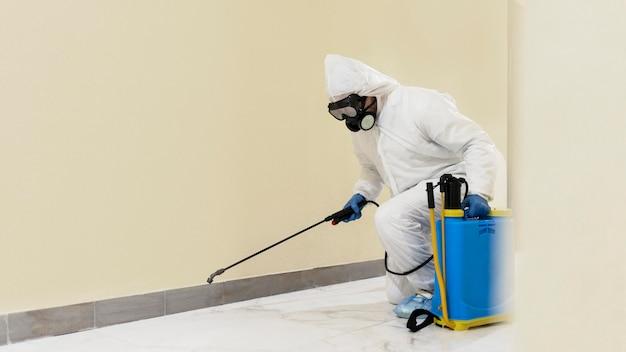 Homem tiro completo desinfetando parede