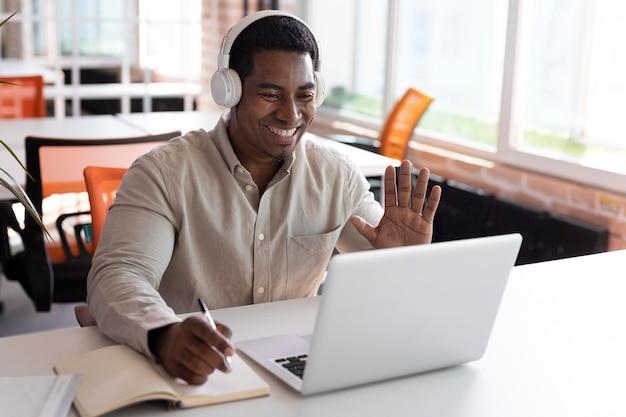 Homem tiro médio acenando para um laptop