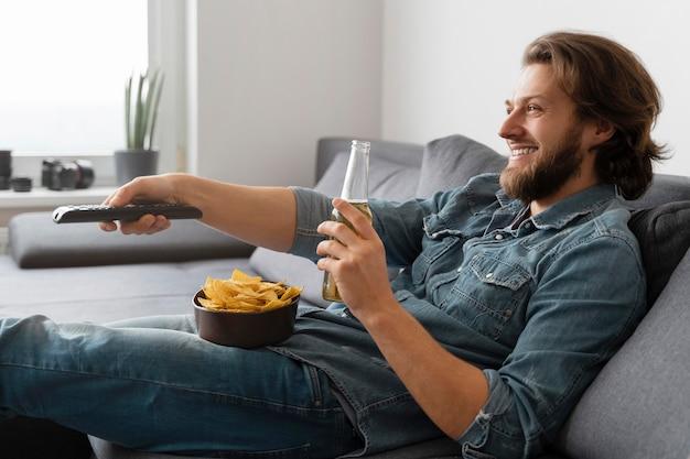 Homem tiro médio com bebida assistindo tv