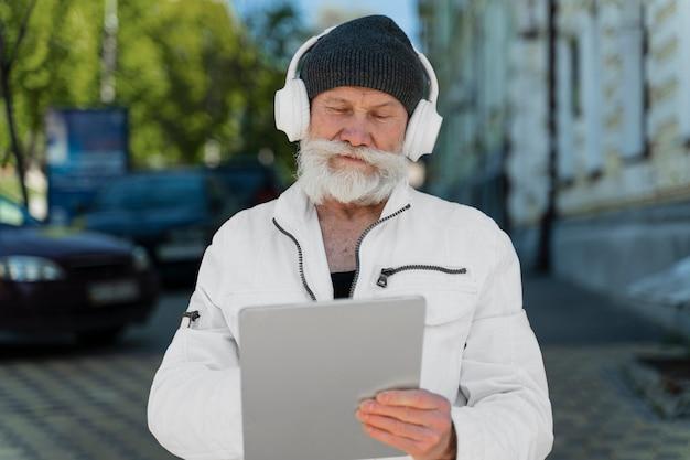 Homem tiro médio com fones de ouvido e tablet