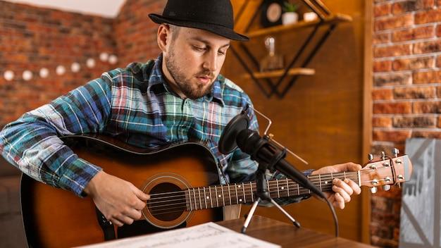 Homem tiro médio com guitarra e microfone