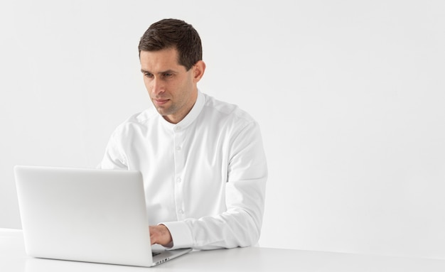 Homem tiro médio com laptop trabalhando