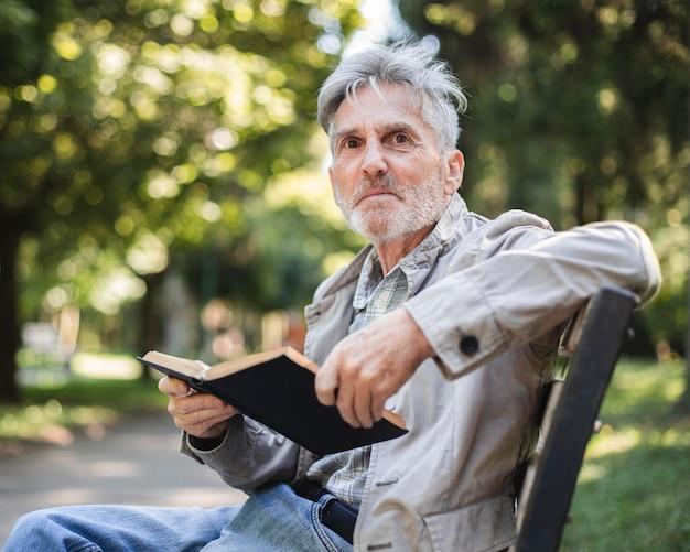 Homem tiro médio com livro ao ar livre
