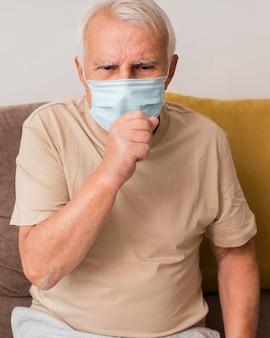Homem tiro médio com máscara tossindo