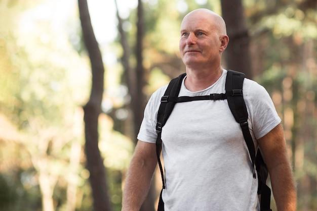Homem tiro médio com mochila na natureza