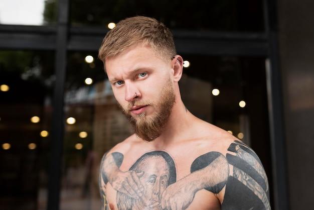 Homem tiro médio com tatuagens ultrapassadas