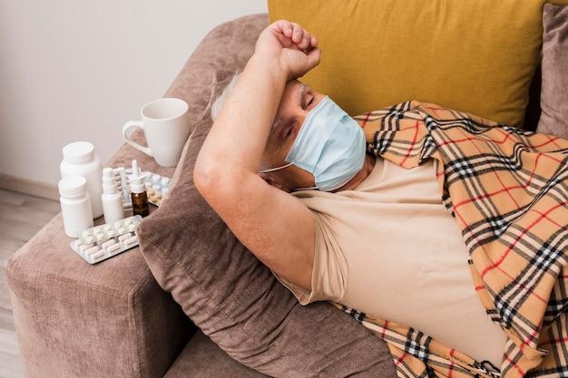 Homem tiro médio deitado no sofá com máscara