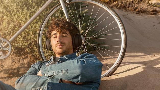 Homem tiro médio deitado perto de uma bicicleta