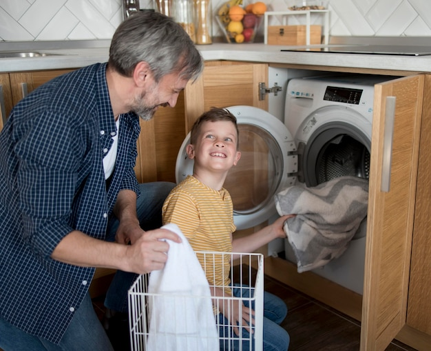 Homem tiro médio e criança lavando roupa