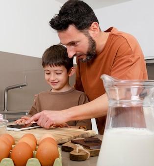 Homem tiro médio e criança na cozinha com tablet