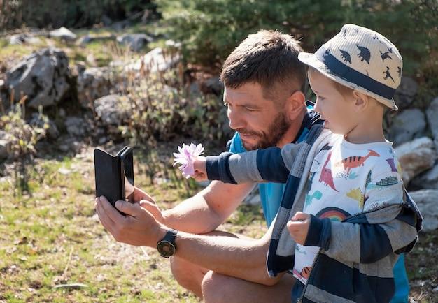 Homem tiro médio e criança tirando uma selfie