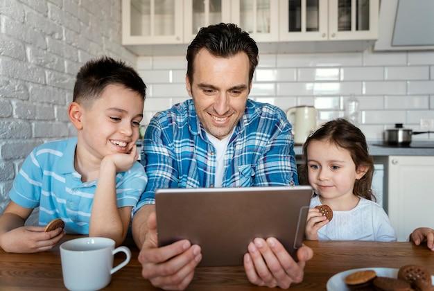 Homem tiro médio e crianças com tablet