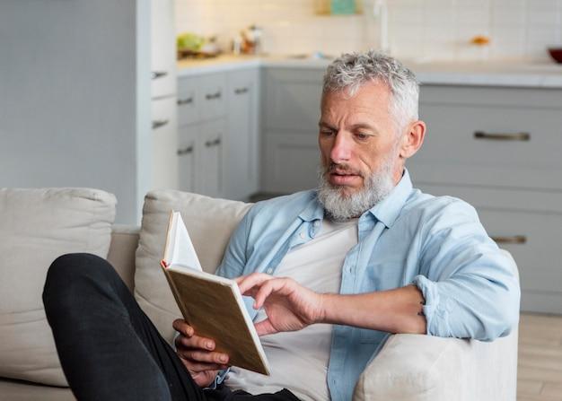 Homem tiro médio lendo no sofá