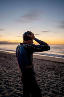 Homem tiro médio na praia ao pôr do sol