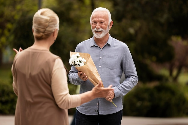 Homem tiro médio oferecendo flores