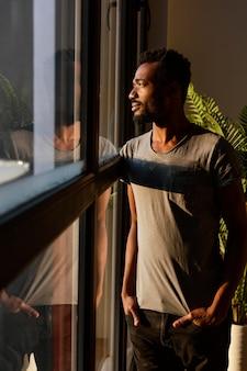 Homem tiro médio posando perto da janela