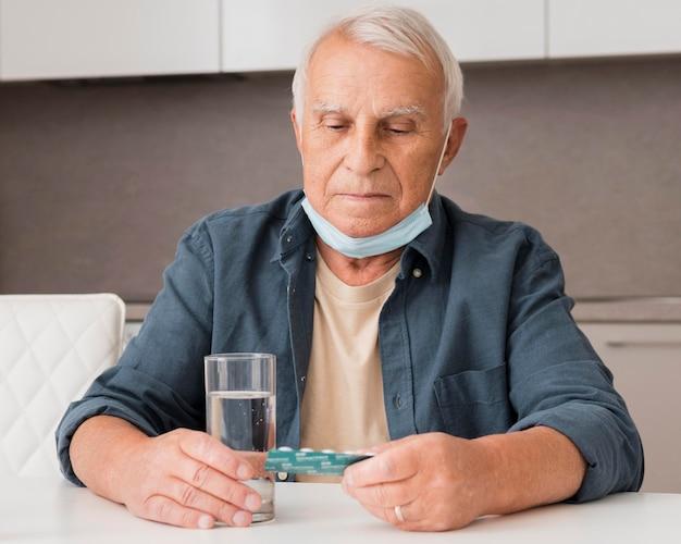 Homem tiro médio segurando bolha de comprimidos
