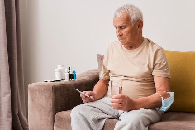 Homem tiro médio segurando comprimidos e copo de água