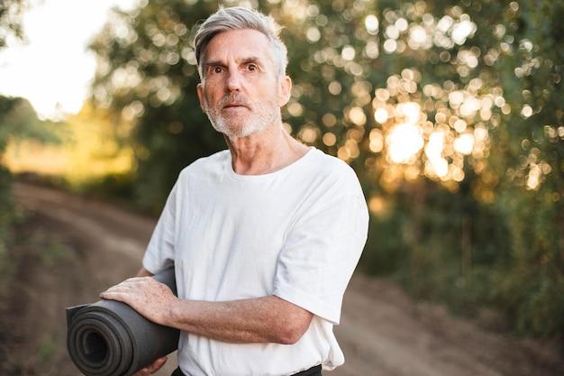 Homem tiro médio segurando tapete de ioga