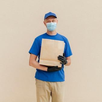 Homem tiro médio segurando um saco de papel