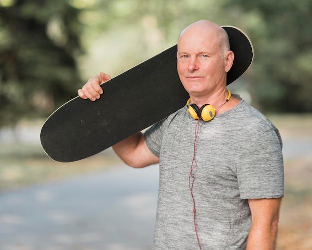 Homem tiro médio segurando um skate