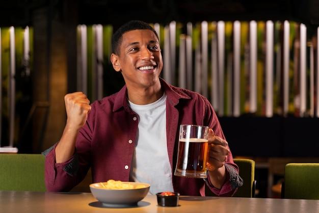 Homem tiro médio segurando uma caneca de cerveja