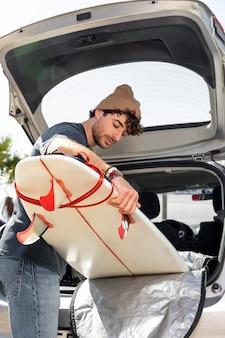 Homem tiro médio segurando uma prancha de surf