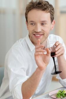 Homem tiro médio segurando uma taça de vinho