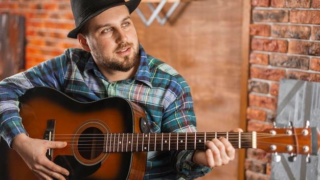 Homem tiro médio segurando violão