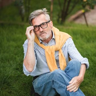 Homem tiro médio sentado na grama