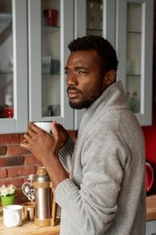 Homem tiro médio tomando café dentro de casa