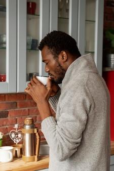 Homem tiro médio tomando café