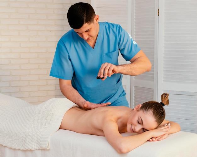 Homem tiro médio usando óleo para massagear