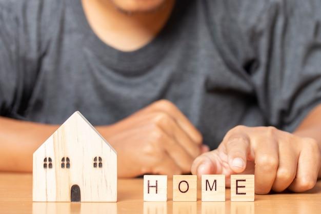 Homem toca a palavra lar com uma casa modelo de madeira