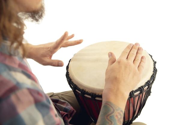 Homem toca bateria étnica darbuka percussão, close-up músico isolado no fundo branco do estúdio. mãos masculinas tocando djembé, bongô no ritmo. instrumentos musicais feitos à mão, som da cultura mundial.