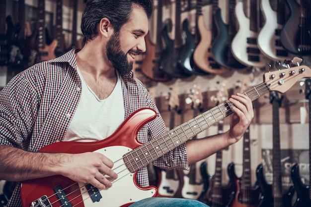 Homem toca guitarra na loja de instrumentos musicais
