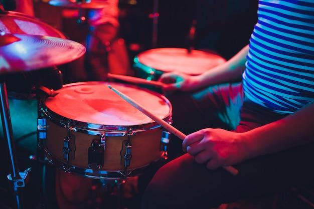 Homem toca instrumento de percussão musical com paus closeup no preto