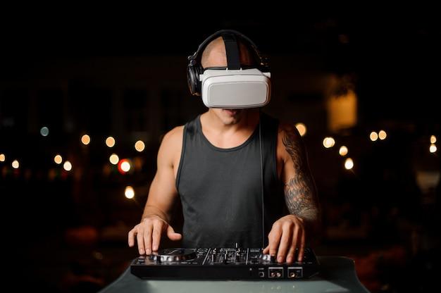 Homem toca um mixer de dj com óculos de realidade virtual.