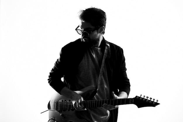 Homem toca uma guitarra elétrica, foto preto e branco