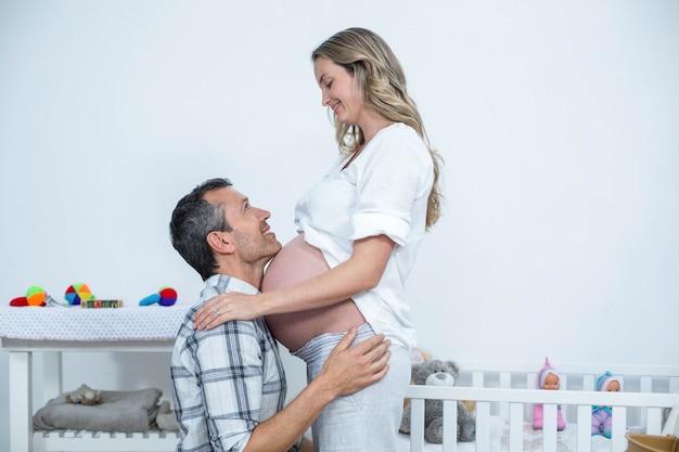 Homem tocando a barriga da mulher grávida em casa