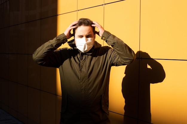 Homem tocando a cabeça e usa máscara protetora contra doenças infecciosas e gripe.