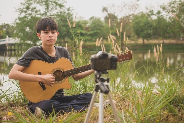 Homem tocando aula de treinamento de violão online, internet com transmissão ao vivo de vídeo do blogger