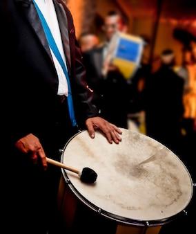 Homem tocando bateria, samba, em festa.