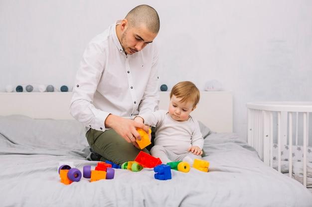 Homem, tocando, com, pequeno, bebê, com, edifício brinquedo, blocos