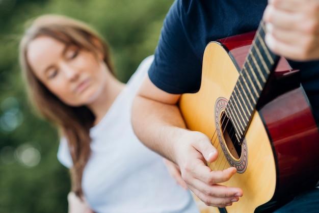 Homem tocando guitarra com mulher no fundo desfocado