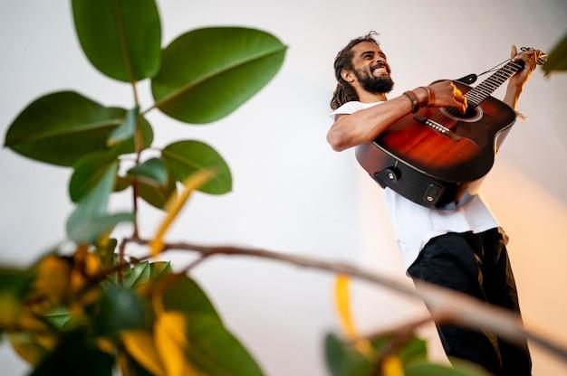 Homem tocando guitarra dentro de casa com espaço de cópia