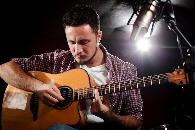 Homem tocando guitarra e microfone desfocado
